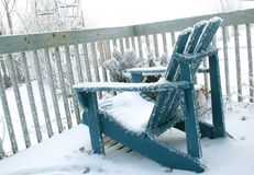 Deck Chair in Winter. Wooden deck chair covered with frost and snow on a frosty morning stock photo