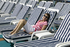 Deck Chairs. View of a women relaxing, laying on a striped deck-chair onboard a ship Royalty Free Stock Images