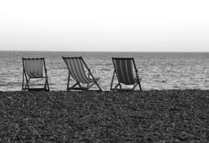 Deck chairs. On the pebble beach of Beer, Devon Royalty Free Stock Photo