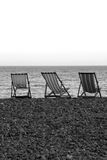 Deck chairs. On the pebble beach of Beer, Devon Royalty Free Stock Image