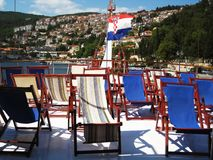 Deck chairs on aft. Many deck chairs on the aft of a sailing ship under the croatian flag at sunny day Stock Image