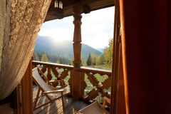 A deck chairs on balcony of the mountain spa resort apartment. Window view at wooden terrace with autumn forest. Background at country house Royalty Free Stock Image