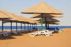 Deck chairs on the beach Stock Photos
