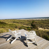 Deck chairs on beach. Two adirondack chairs on wooden deck overlooking beach at Bald Head Island, North Carolina Stock Photo