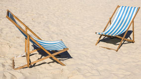 Deck chairs on the beach Stock Images
