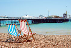 Deck chairs on the beach Brighton England. With pier in the background Stock Photos