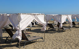 Deck chairs on the beach with the curtains to shelter from the h Royalty Free Stock Image