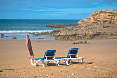 Deck chairs on the beach Stock Photos