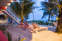 Deck-chairs by the beach. A night photo of three deck-chairs set by the beach and right out of a great hotel painted in pink Stock Photo