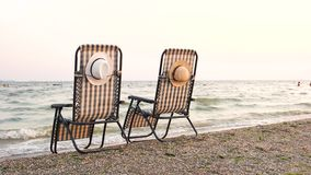 Deck chairs on beach seashore. Attached hats. Rear back view stock video