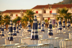 Deck-chairs and beach umbrellas on beach Stock Images
