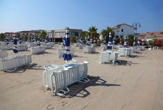 Deck chairs and beach umbrellas are on empty beach Stock Photos