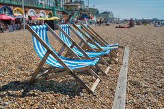 4 deck chairs on Brighton beach. 4 blue deck chairs on Brightons pebble beach Stock Photography