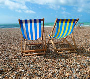 Deck chairs on Brighton Beach, UK. Two striped deck chairs on Brighton Beach, UK Royalty Free Stock Photos