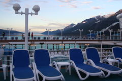 Deck chairs on a cruise ship in Alaska. Blue and white lounge chairs on a cruise to Alaska with snowy mountains in background Royalty Free Stock Photo