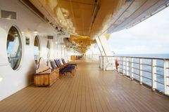 Deck chairs on a cruise ship. With circular windows in the back Stock Photo