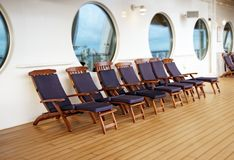 Deck chairs on a cruise ship. With circular windows in the back Royalty Free Stock Photography