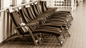 Deck chairs on cruise ship. These deck chairs don't get much action on a chilly Alaska cruise. But someone did leave a bag on one Royalty Free Stock Images