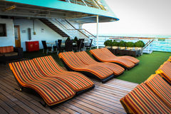Deck chairs on cruise ship. Row of orange striped deck chairs on cruise ship Royalty Free Stock Images