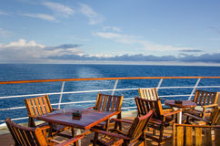 Deck chairs on cruise ship. Wooden deck chairs and tables on the outdoor deck of a cruise ship Royalty Free Stock Photo