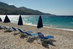 Deck chairs on empty beach Stock Photos