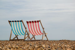 2 Deck Chairs Facing the Sea on Brighton Beach, England. Landscape shot of 2 stripy deck chairs on a shingle beach in England looking out to sea stock photos