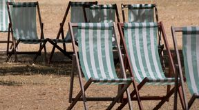 Deck chairs with green and white stripes on dead grass in Hyde Park, London during the summer heatwave, July 2018. royalty free stock images