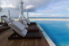 Deck chairs at infinity pool of Maldives Royalty Free Stock Image