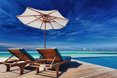 Deck chairs and infinity pool over tropical lagoon Royalty Free Stock Images