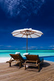 Deck chairs and infinity pool over tropical lagoon stock images