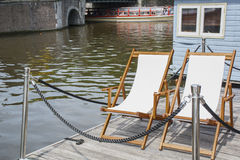 Deck chairs near the canal in Amsterdam Royalty Free Stock Photography