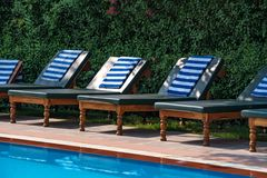 Deck chairs near the open swimming pool. Deck chairs near the swimming pool with beautiful blue water stock photo