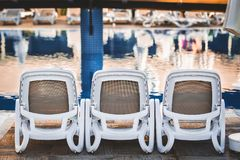 Deck chairs near the pool. White plastic deck chairs standing in front of each other near the swimming pool with blue tile stock photography