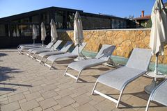 Deck chairs in the resort pool, Italy. Deck chairs near swimming pool and on summer resort, Tuscany, Italy. Sunset light stock photo