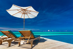 Deck chairs overlooking infinity pool and tropical lagoon Royalty Free Stock Photo