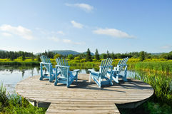 Deck Chairs Overlooking Wetlands. Four empty blue wooden adirondack chairs sitting on wooden deck overlooking lush wetlands. Thunder Bay, Ontario, Canada. Blue Stock Photography