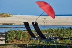 Deck chairs and a parasol stock photo