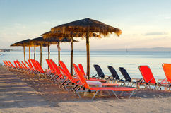 Deck chairs and parasols on sea beach in summer Royalty Free Stock Photo