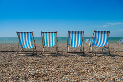 4 deck chairs on a pebble beach. 4 blue deck chairs on a pebble beach Stock Photography