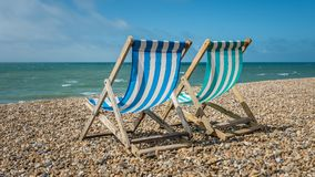 Deck chairs on a pebble beach stock photo