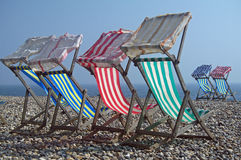 Deck chairs on Pebble Beach Royalty Free Stock Photos