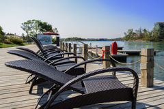 Deck chairs on planked dock in sunny afternoon Royalty Free Stock Image