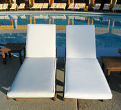 Deck Chairs at Resort Pool. A pair of deck chairs in front of a pool at a resort hotel stock photos