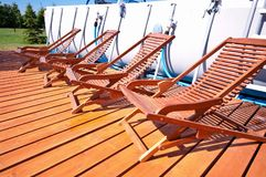 Deck chairs. A row of deck chairs on a patio by a swimming pool Stock Image