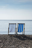Deck Chairs at The Seaside. Two striped deck chairs at the beach at Beer, Devon, UK Royalty Free Stock Image