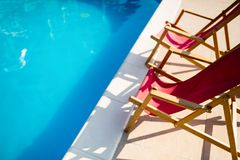 Deck chairs at side of pool. Symbolizing summer vacation stock images