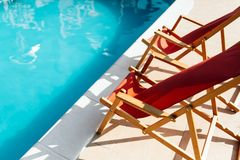 Deck chairs at side of pool. Symbolizing summer vacation stock photography