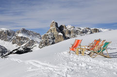 Deck chairs in the snow. With the dolomites in the background Royalty Free Stock Image