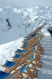 Deck chairs standing on peak in Alps in winter Stock Images