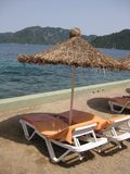 Deck chairs and  straw sunshade Royalty Free Stock Photo